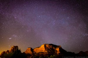 The night sky in Sedona, Az. with the red rock formations in the foreground.
